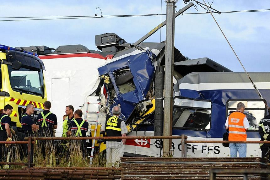 Rescuers work on the site of a train accident on July 29, 2013 in Granges-pres-Marnand, western Switzerland. Two trains collided head-on Monday in western Switzerland, injuring 35 passengers, at least five of them seriously, police said. -- PHOTO: AF