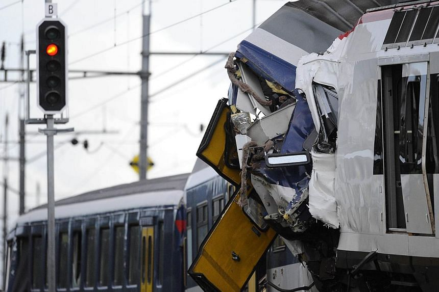 A picture shows the site of a train accident on July 29, 2013 in Granges-pres-Marnand, western Switzerland. Two trains collided head-on, injuring 40 passengers, at least five of them seriously, police said. -- PHOTO: AFP