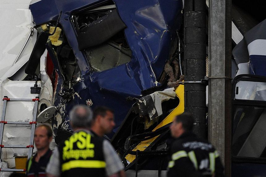Rescuers works on the site of a train accident on July 29, 2013 in Granges-pres-Marnand, western Switzerland. Two trains collided head-on, injuring 40 passengers, at least five of them seriously, police said. -- PHOTO: AFP