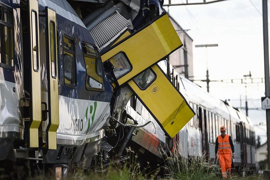 Rescue personnel work at the site where two passenger trains collided head-on in Granges-pres-Marnand, western Switzerland, on Monday, July 29, 2013. Police say at least 44 people were injured, four of them seriously. -- PHOTO: AP