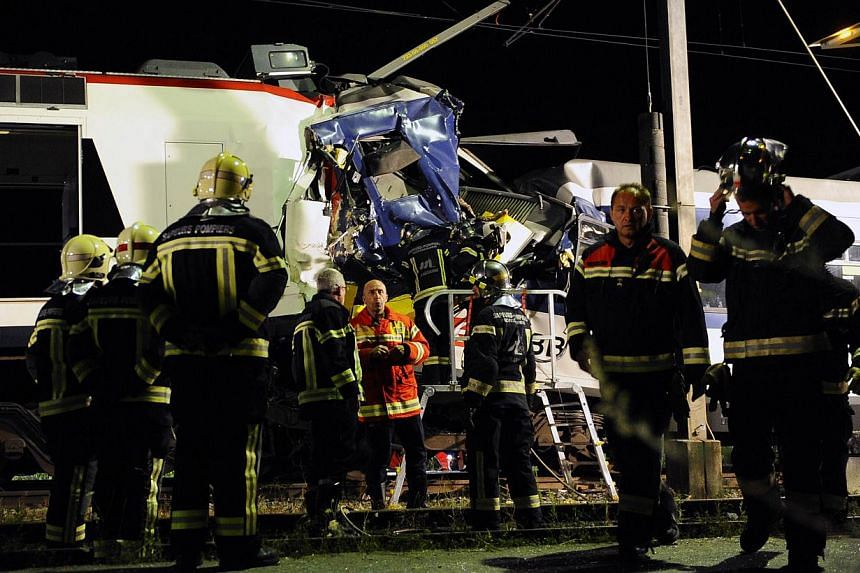 Rescuers work on the site of a train accident on July 29, 2013 in Granges-pres-Marnand, western Switzerland. Two trains collided head-on, injuring 40 passengers, at least five of them seriously, police said. -- PHOTO: AFP