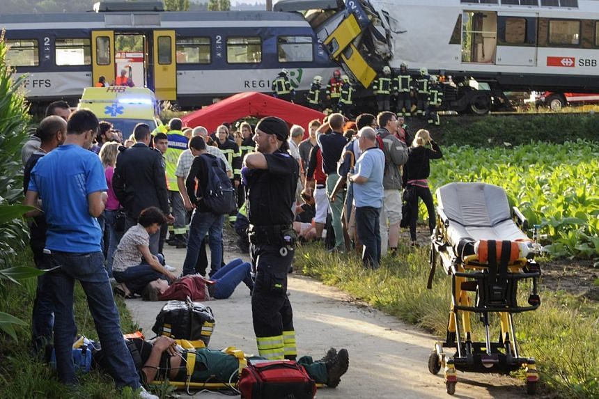 Injured passengers are helped at the site where two passenger trains collided head-on in Granges-pres-Marnand, western Switzerland, on Monday, July 29, 2013. Police say at least 44 people were injured, four of them seriously. -- PHOTO: AP