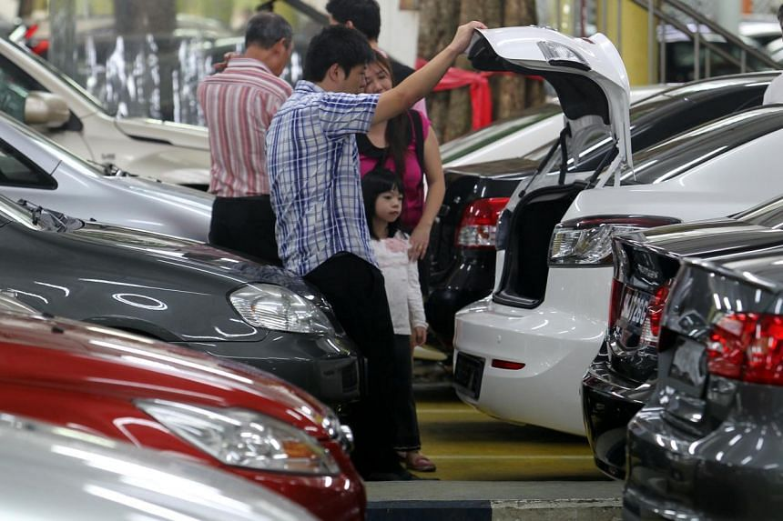 Visitors at a used car showroom at Turf City on April 6, 2013. An increasing number of Singaporeans are taking out two or more loans, according to data from the Credit Bureau Singapore. -- ST PHOTO: SEAH KWANG PENG