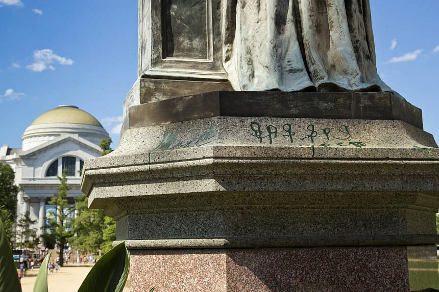 Green paint is seen on the pedestal of the statue of Joseph Henry, outside the headquarters of the Smithsonian Institution on the National Mall in Washington, on Monday, July 29, 2013. US police arrested a female suspect Monday after three iconic Was