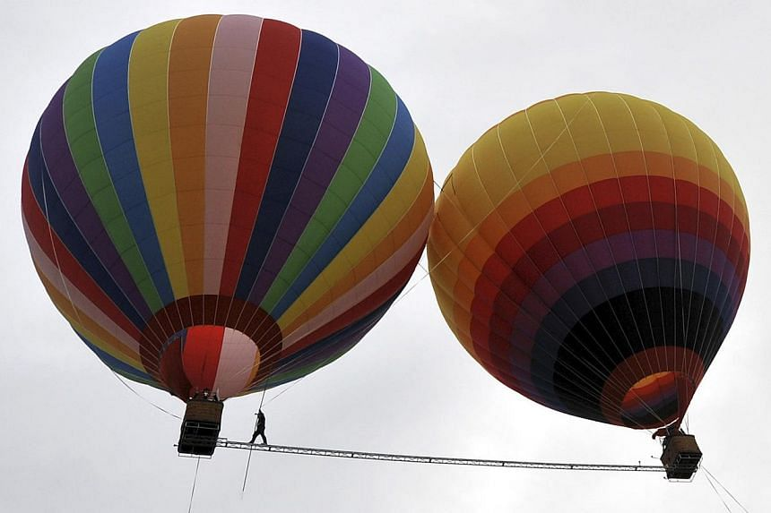 Aisikaier Wubulikasimu, 40-year-old Uighur acrobat, walks on a 18m long, 50mm wide tightrope strung between two hot air balloons, in Shilin county, Yunnan province on Tuesday, July 30, 2013. See more pictures from around the world in Through The Lens
