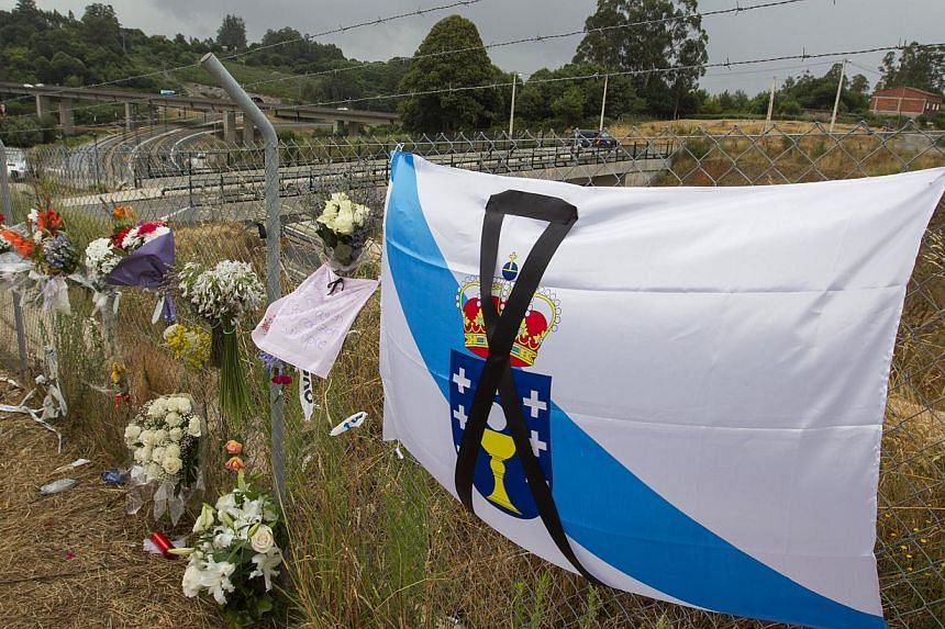 Bouquets and a Galician type flag with a black ribbon signalling mourning are seen by the train crash site in Santiago de Compostela, Spain, Sunday July 28, 2013. Hundreds of mourners gathered Monday at a memorial mass for the 79 people killed in Spa