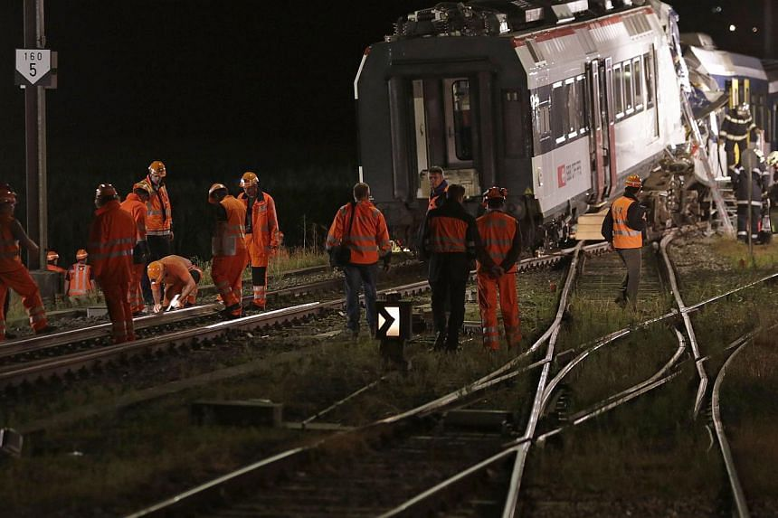 Swiss Federal Railways (SBB) staff inspect the rails after removing carriages at the site of a head-on collision between two trains near Granges-pres-Marnand, near Payerne in western Switzerland on July 29, 2013. Rescue workers at the site of the Swi