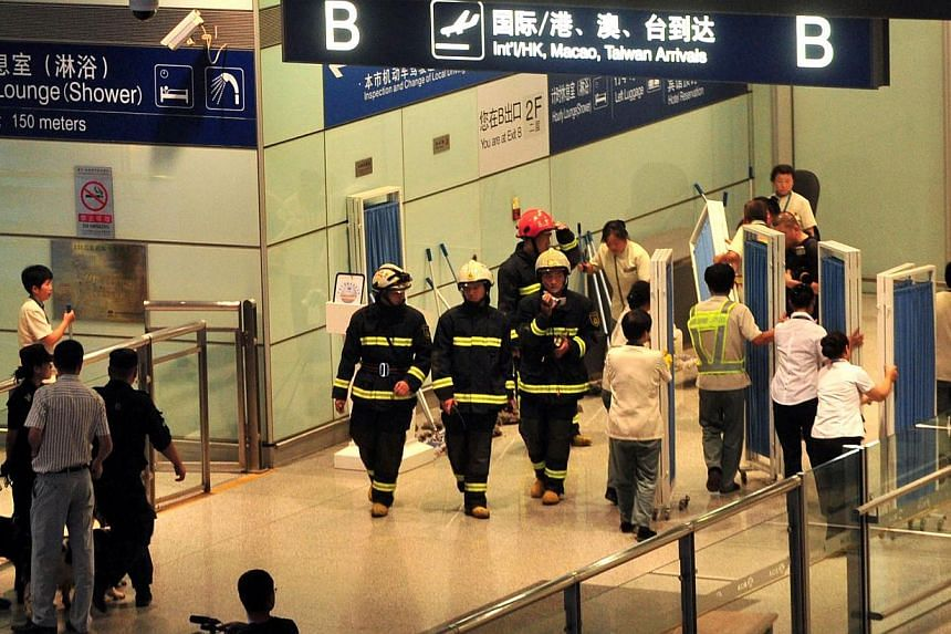 Chinese security personnel move in to investigate the scene where a man in a wheelchair ignited a home-made explosive device at Beijing's international airport, injuring himself but no others on Saturday, July 20, 2013. A disabled man who bombed Beij
