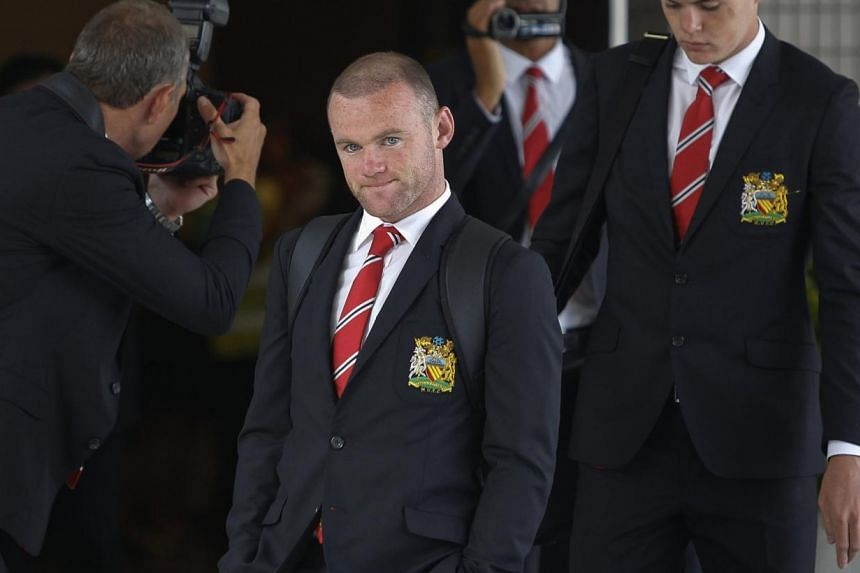 Manchester United's Wayne Rooney arrives at Don Muang International Airport, ahead of Saturday's soccer friendly against the Thailand Singha All Stars as part of the team's Asia tour in Bangkok on July 11, 2013. -- PHOTO: REUTERS