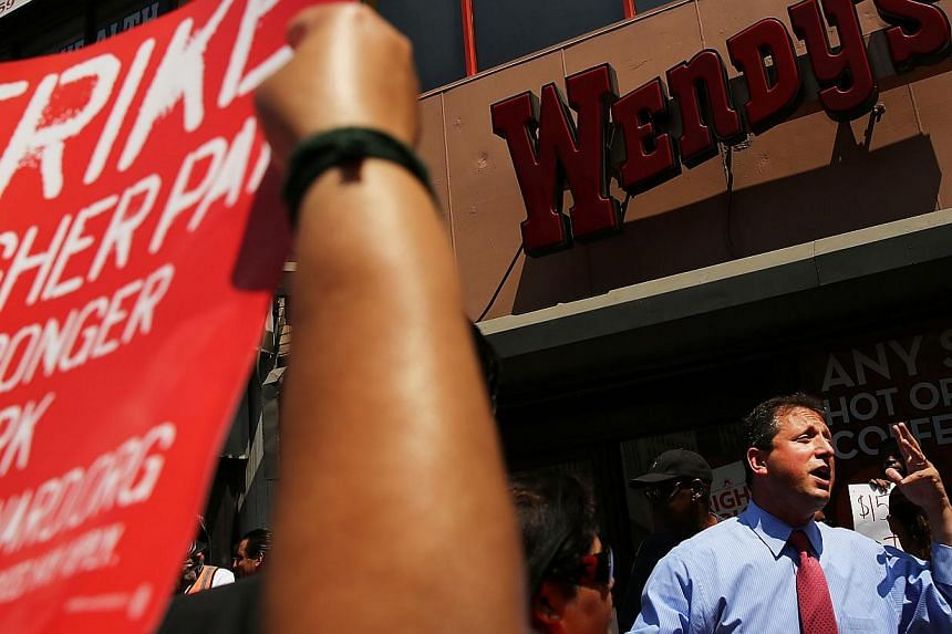 New York City Councilman Brad Lander speaks to employees at Wendy's fast-food restaurant during a demonstration outside of one of the restaurants to demand higher pay and the right to form a union on July 29, 2013 in New York City. -- PHOTO: AFP
