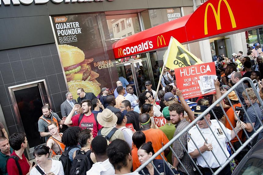 Demonstrators in support of fast food workers protest outside a McDonald's as they demand higher wages and the right to form a union without retaliation Monday, July 29, 2013, in New York's Union Square. Hundreds of workers at McDonald's and other fa