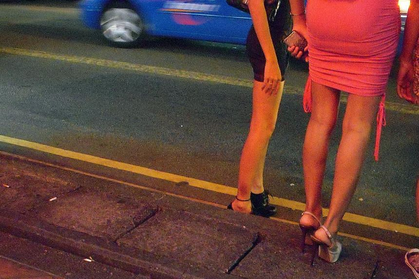 Foreign prostitutes ply their trade along Geylang Road in this June 1, 2011 photo. Larry Tan Swee Lai, 51, was jailed four months for procuring women for prostitution and living off their earnings. -- ST FILE PHOTO: DESMOND WEE