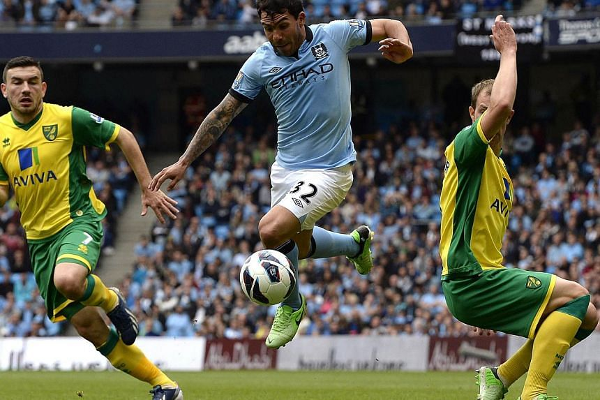 Norwich City's Steven Whittaker (right) and Robert Snodgrass (left) challenge Manchester City's Carlos Tevez (centre) during their English Premier League football match in Manchester, northern England May 19, 2013. SingTel has launched a new ap
