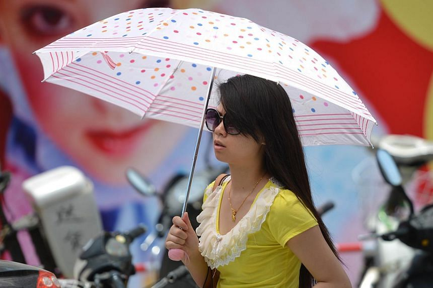 A woman holds an umbrella to protect herself from the sun as a heatwave hits Shanghai on July 4, 2013. The Shanghai Meteorological Bureau issued heatwave warnings as temperatures reached as high as 38 degrees celcius in the city in recent days accord