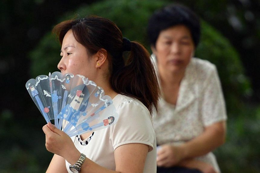 A woman uses a fan to keep cool as a heatwave continues in Shanghai on July 24, 2013. The Shanghai Meteorological Bureau issued heatwave warnings as temperatures reached as high as 38 degrees Celcius (101F) in the city in recent days according to sta