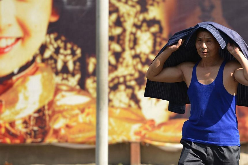 A pedestrian uses his jacket to shelter from the sun as a heatwave continues in Shanghai on July 24, 2013. More than 10 people have died in China's commercial hub Shanghai, a local health official said on Wednesday, as the city grapples with its high