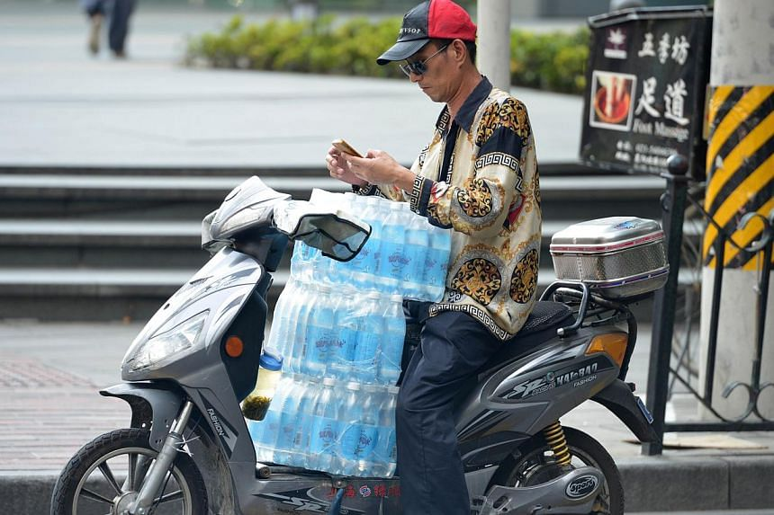 A motorcyclist carries bottled water on his scooter as a heatwave continues in Shanghai on July 24, 2013. The Shanghai Meteorological Bureau issued heatwave warnings as temperatures reached as high as 38 degrees Celcius (101F) in the city in recent d