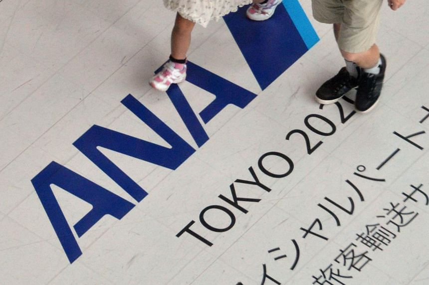 Passengers walk over a logo sign for All Nippon Airways (ANA) at Tokyo's Haneda Airport on July 30, 2013. Japan's ANA Holdings Inc plans to beef up its low-cost-carrier operations by focusing on resort travel to places such as Guam and Hawaii, the Ni