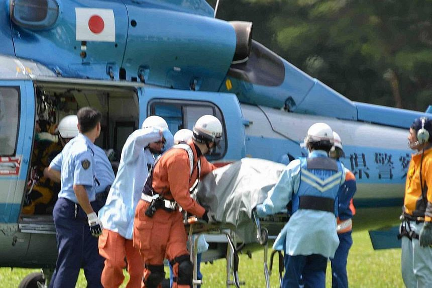 Rescue workers transport an unconscious South Korean hiker on a stretcher from a helicopter in Komagane, in this photo taken by Kyodo on July 30, 2013. Japanese police on Wednesday said they had retrieved the body of a fourth South Korean climber who
