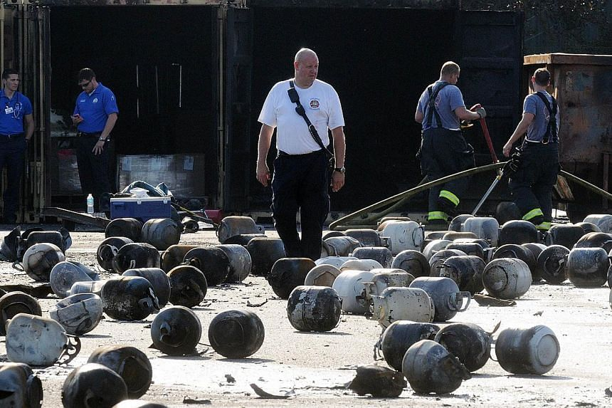 Firefighters walk through propane cylinders on the grounds of Blue Rhino, a propane gas company, after a series of explosions rocked the central Florida propane gas plant, on July 30, 2013 in Tavares, Florida. The explosions occurred late last night,
