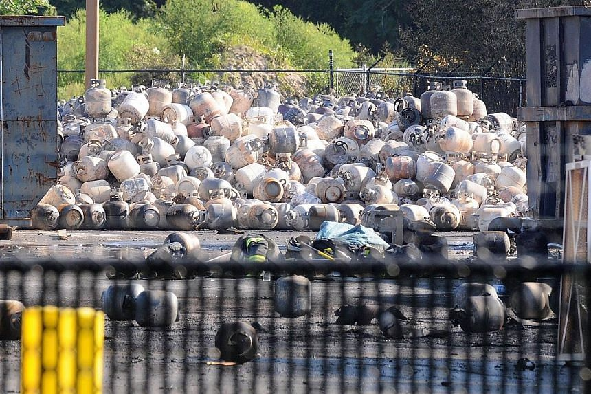 Propane cylinders lie on the grounds of Blue Rhino, a propane gas company, after a series of explosions rocked the central Florida propane gas plant, on July 30, 2013 in Tavares, Florida. The explosions occurred late last night, injuring eight worker