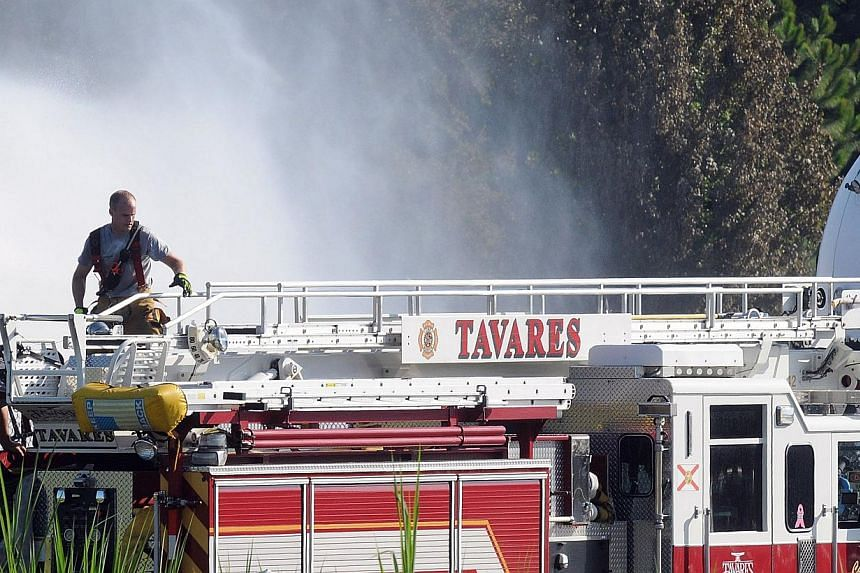 A Lake County firefighter works after a series of explosions rocked Blue Rhino, a central Florida propane gas plant, on July 30, 2013 in Tavares, Florida. The explosions occurred late last night, injuring eight workers. -- PHOTO: AFP