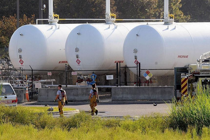 Firefighters walk past propane cylinders on the grounds of Blue Rhino, a propane gas company, after a series of explosions rocked the central Florida propane gas plant, on July 30, 2013 in Tavares, Florida. The explosions occurred late last night, in