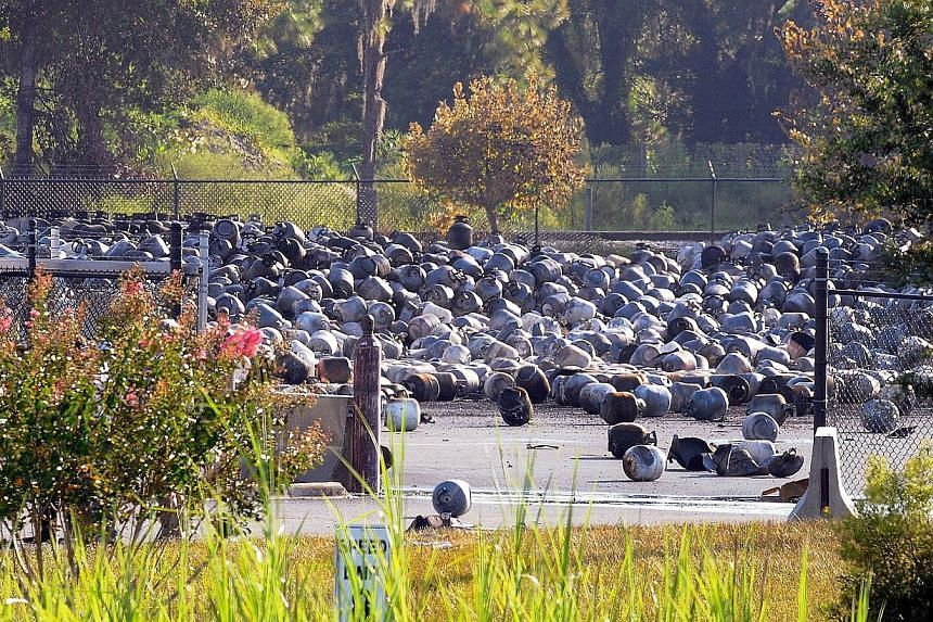 Propane cylinders lie on the grounds of Blue Rhino, a propane gas company, after a series of explosions rocked the central Florida propane gas plant, on July 30, 2013 in Tavares, Florida. A series of explosions shook a propane gas plant in central Fl