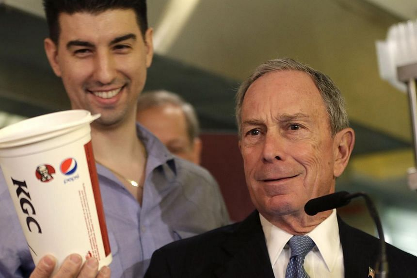 New York City mayor Michael Bloomberg looks at a 64oz cup, as Lucky's Cafe owner Greg Anagnostopoulos (left), stands behind him on March 12, 2013. Mr Bloomberg's controversial plan to keep large sugary drinks out of restaurants and other eateries was
