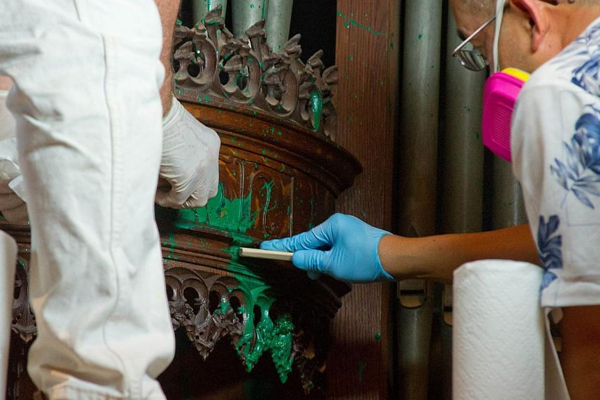 Workers clean green paint from the organ in the Bethlehem Chapel at the National Cathedral on July 30, 2013 in Washington, DC. A Chinese woman appeared in a Washington court for splattering green paint inside the National Cathedral the day before. --