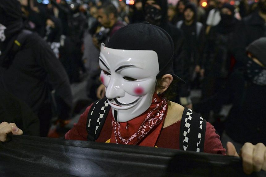 A demonstrator wearing a Guy Fawkes mask takes part in a protest in support of Rio de Janeiro's protests and against Sao Paulo's governor Geraldo Alckmin, on July 30, 2013, in Sao Paulo. -- PHOTO: AFP