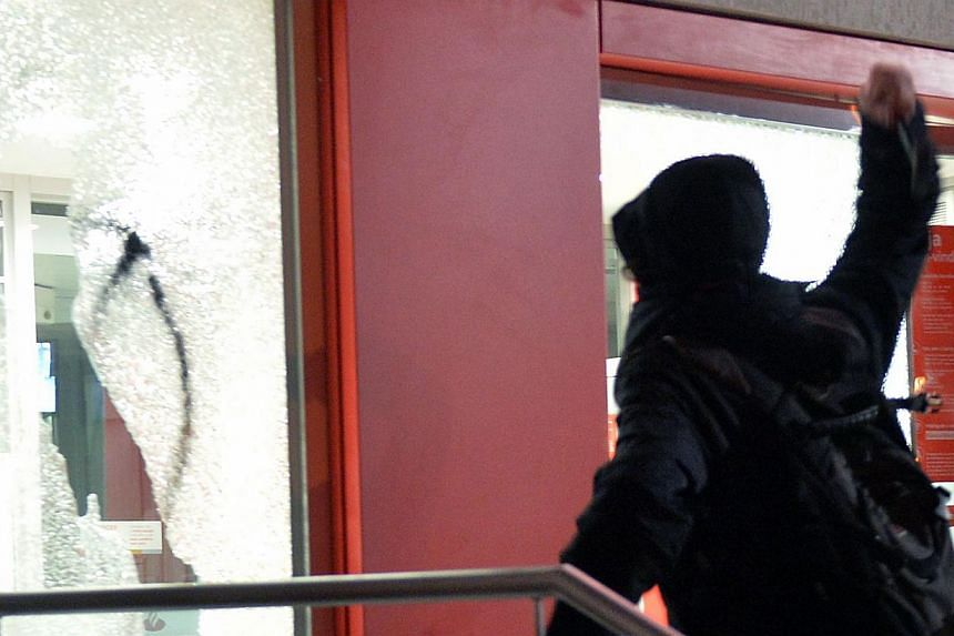 A demonstrator breaks a window glass of a bank office, during a protest in support of Rio de Janeiro's protests and against Sao Paulo's governor Geraldo Alckmin, on July 30, 2013, in Sao Paulo. -- PHOTO: AFP