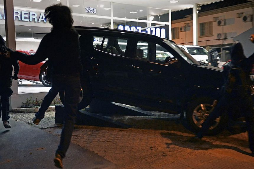 Demonstrators attack a car on display outside a cars company, during a protest in support of Rio de Janeiro's protests and against Sao Paulo's governor Geraldo Alckmin, on July 30, 2013, in Sao Paulo. -- PHOTO: AFP