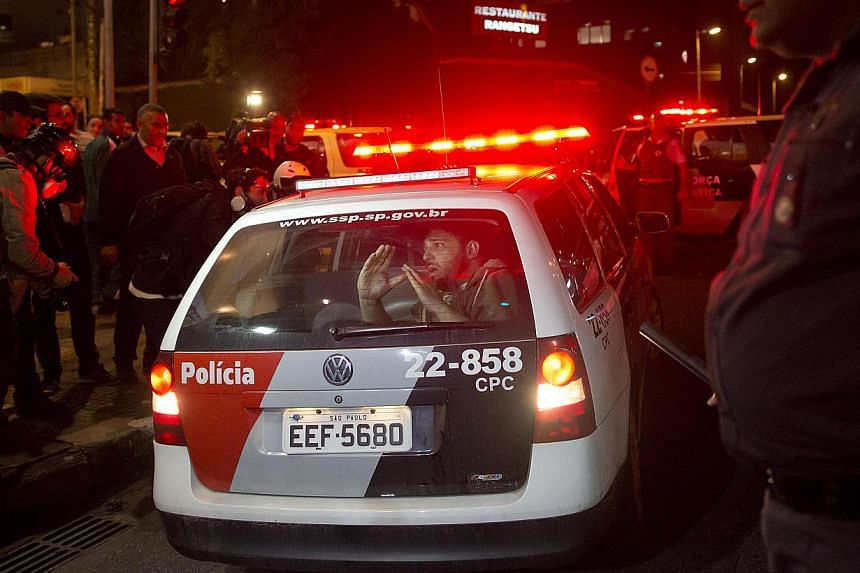 An anti-government demonstrator gestures to fellow protesters from the back seat of a police vehicle after he was detained in Sao Paulo, Brazil, on Tuesday, July 30, 2013. Demonstrators are demanding better public transit, health and education servic