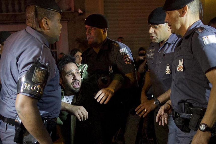 An anti-government demonstrator is detained by the police during a protest in Sao Paulo, Brazil, on Tuesday, July 30, 2013. Demonstrators are demanding better public transit, health and education services. -- PHOTO: AP