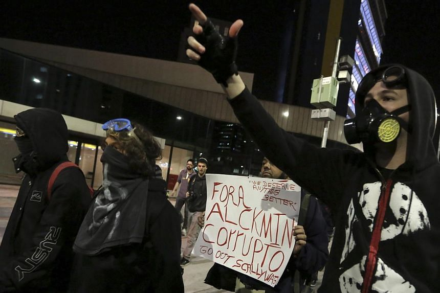 """Demonstrators of the group called Black Bloc shout slogans during a protest against Sao Paulo State Governor Geraldo Alckmin, in Sao Paulo on July 30, 2013. The placard reads, """"Out Sao Paulo State Governor Alckmin, Corrupt"""". -- PHOTO: REUTERS"""