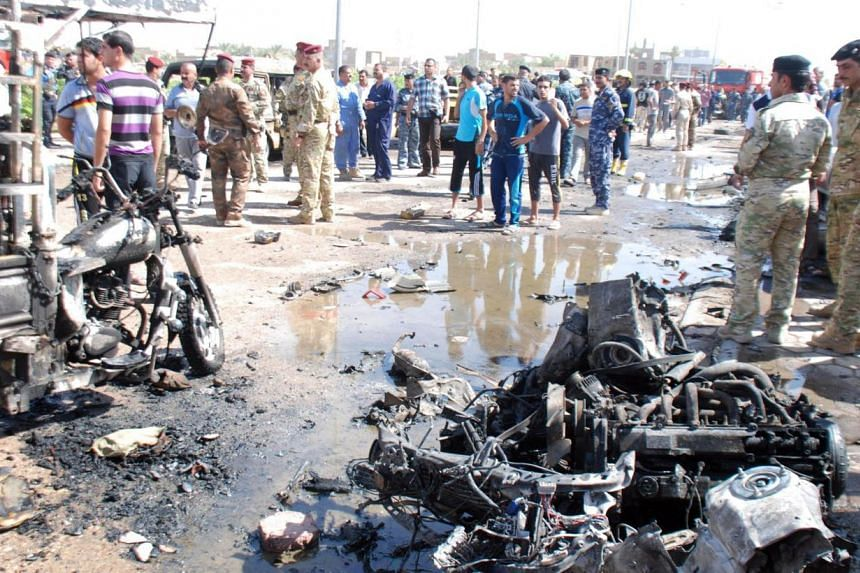 Iraqi army personnel and people gather at the site of a car bomb attack in the city of Kut, 150km south-east of Baghdad, July 29, 2013. An Al-Qaeda-affiliated group claimed responsibility for a wave of bombings across Iraq that killed 60 people on Mo