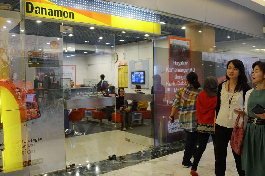 People walk past a branch of Bank Danamon in Jakarta on Thursday, May 23, 2013. DBS Group Holdings' torturous attempt to acquire Bank Danamon Indonesia looks is likely to have foundered. -- FILE PHOTO: AFP