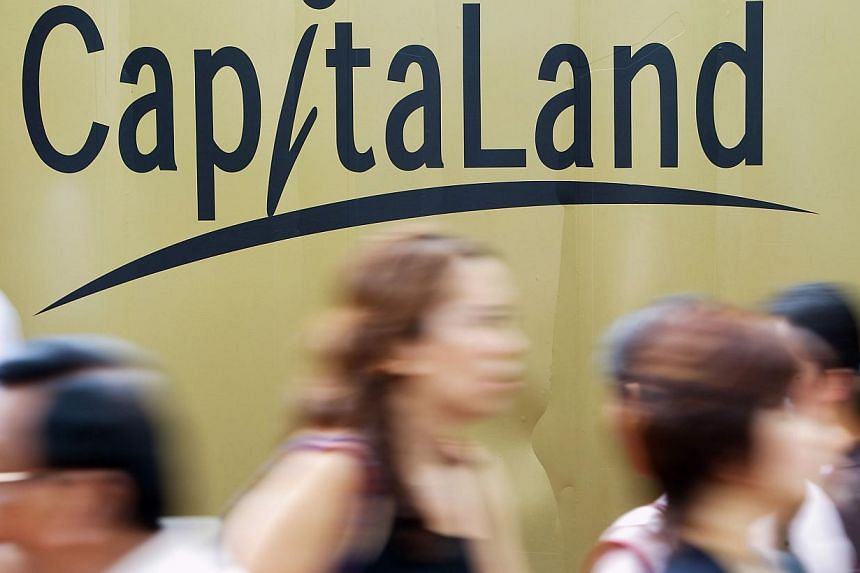 Pedestrians walk past a billboard with CapitaLand Ltd.'s logo in Singapore, on Wednesday, Feb 14, 2007. Property giant CapitaLand has managed to save over $35 million in utility costs through its sustainability programme since 2009, it said on Wednes