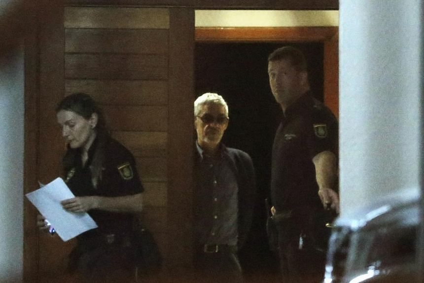 Police stand guard as train driver Francisco Jose Garzon Amo (centre) leaves the court following his release in Santiago de Compostela, Spain on Sunday, July 28, 2013. The driver of a Spanish train that derailed killing 79 people told a judge he didn