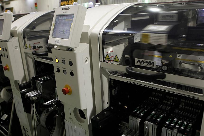 Robotic chip mounters are seen at Panasonic Factory Solutions in Showa town, Yamanashi prefecture on April 19, 2013. As the breakneck growth in the global smartphone market eases, the mostly Japanese companies that make the robots that build the phon