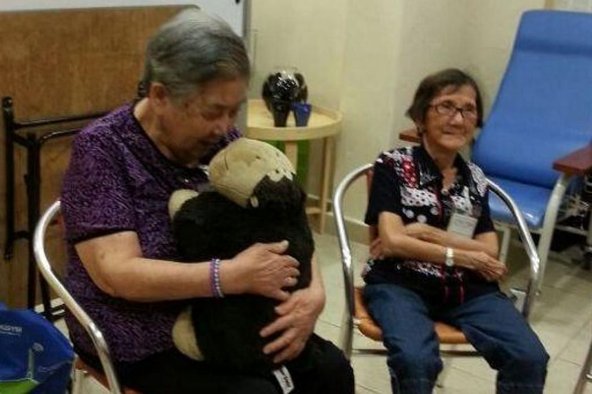 Elderly patients can now reap the benefits of pet therapy from a robot instead of live animals. The device, called the Huggler, emits a variety of sounds when stroked, tickled, or squeezed. -- ST PHOTO: AUDREY TAN