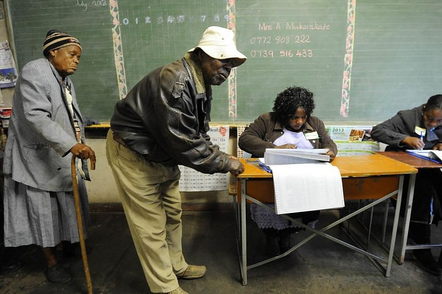 Zimbabweans arrive to vote at a polling booth in a school in Harare on Wednesday, July 31, 2013. -- PHOTO: AFP