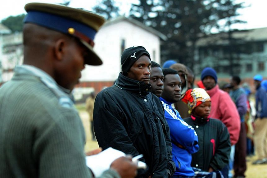 A policeman stands as Zimbabweans line up near a polling station in Harare to vote in a general election on Wednesday, July 31, 2013. -- PHOTO: AFP