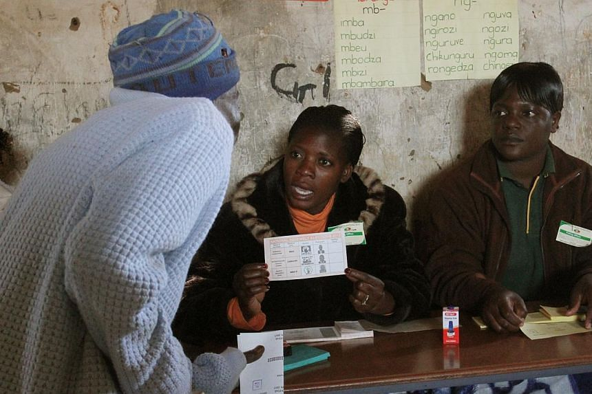 Electoral officers explain voting procedures to an elderly voter as the country went to the polls in a Harare suburb on Wednesday, July 31, 2013. -- PHOTO: AP