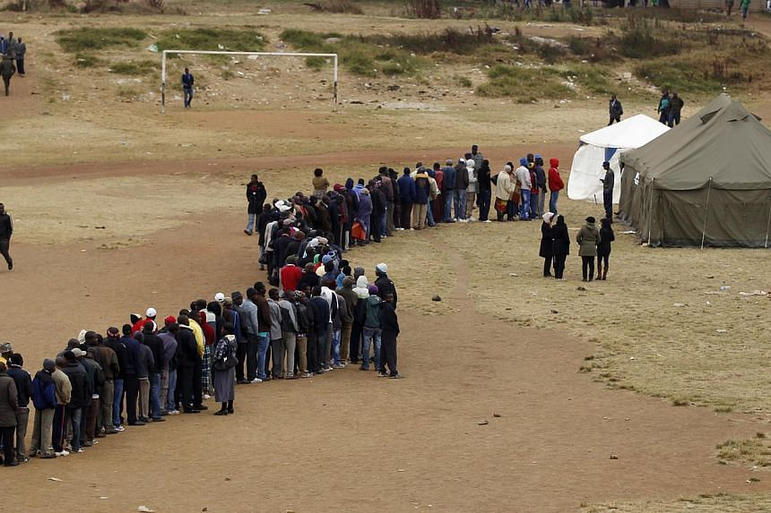 Zimbabweans wait in line to cast their votes in Mbare township outside Harare on Wednesday, July 31, 2013. Crisis-weary Zimbabweans flocked to cast their ballots on Wednesday in a fiercely contested election overshadowed by accusations of vote-riggin