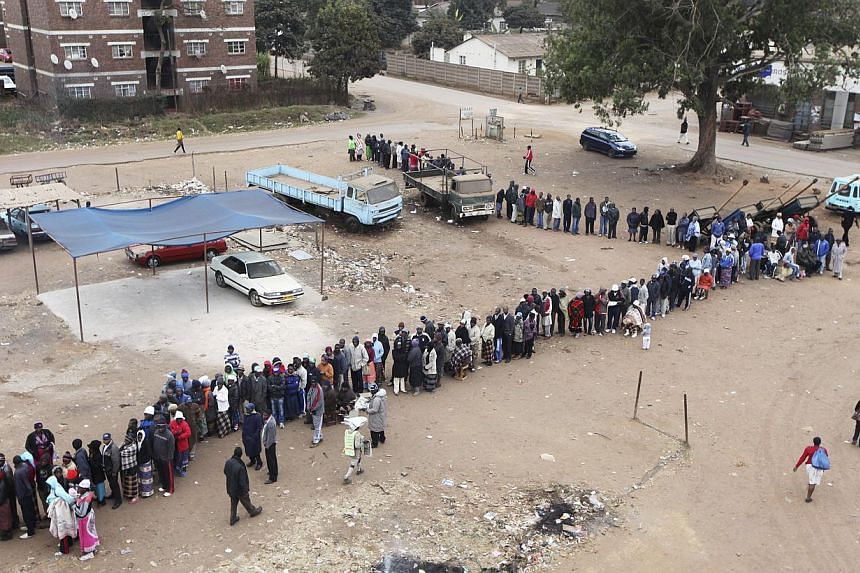 Zimbabweans wait to cast their votes in presidential and parliamentary elections in Harare on Wednesday, July 31, 2013. -- PHOTO: AP