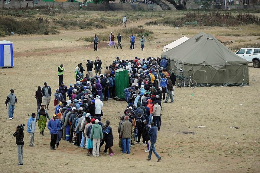 Zimbabweans line up in front of a temporary polling station in Harare to vote in a general election on Wednesday, July 31, 2013. -- PHOTO: AFP
