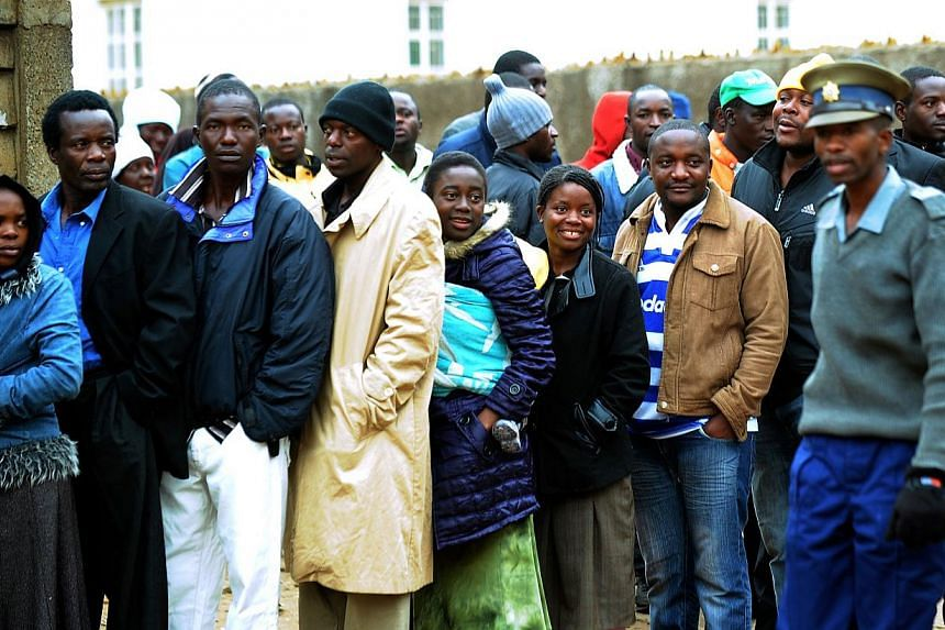 Zimbabweans line up near a polling station in Harare to vote in a general election on Wednesday, July 31, 2013. -- PHOTO: AFP
