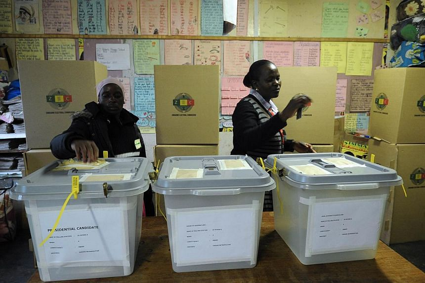 Two women cast their vote at a polling booth in a school in Harare on Wednesday, July 31, 2013. -- PHOTO: AFP